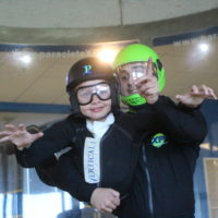 Young child loving the birthday party idea of indoor skydiving.