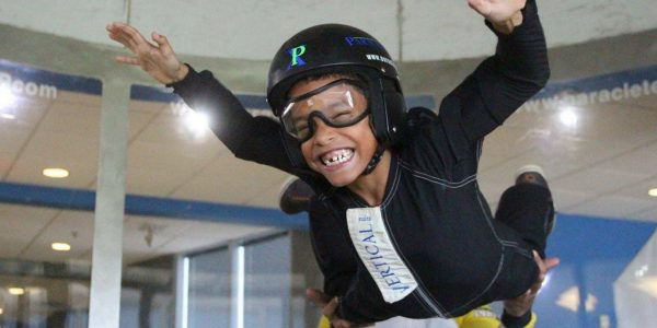young kid flies in indoor skydiving wind tunnel