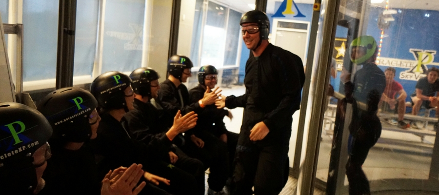 man high-fives indoor skydiving guests after flight