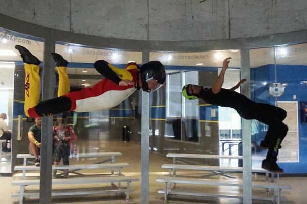 two flyers perform advanced indoor skydiving maneuvers