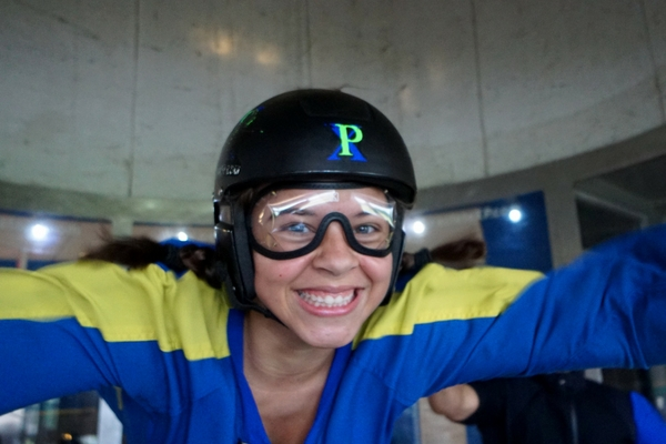 woman grins ear to ear indoor skydiving