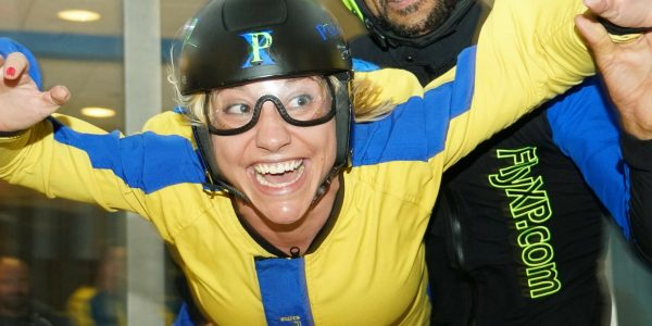 woman excitedly indoor skydiving first time