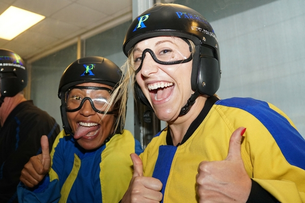 two women giving thumbs up after indoor skydive