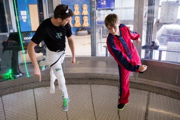 younger boy receives indoor skydiving tips from coach