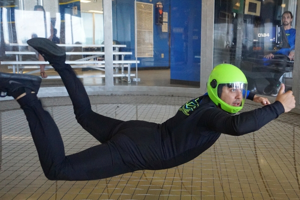 instructor demonstrates indoor skydiving techniques