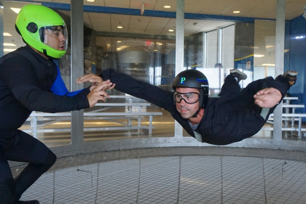 man receives hands-on instruction during first indoor skydive