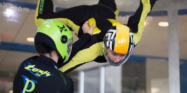 indoor skydiver receives coaching in the tunnel