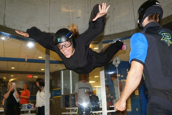woman smiles trying indoor skydiving first time