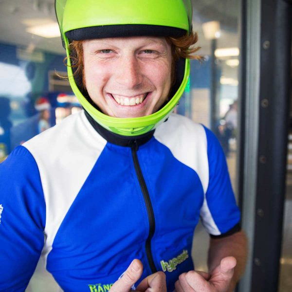 indoor skydiving instructor smiles in front of wind tunnel
