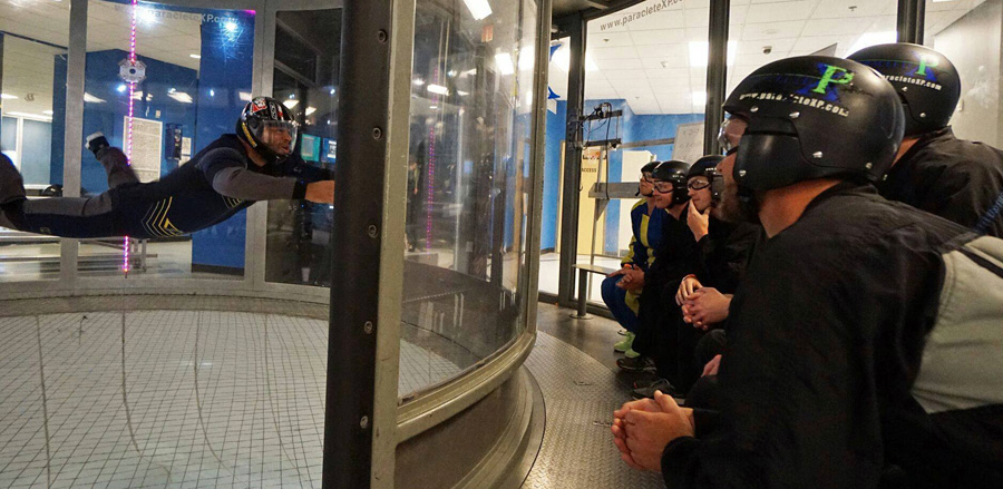 indoor skydiving instructor demonstrates the tunnel to students