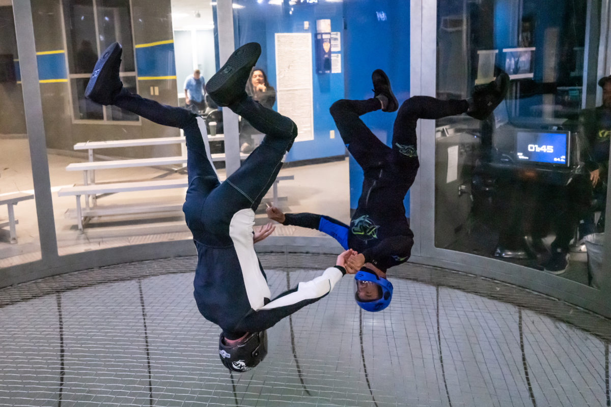 Two people fly upside-down in the wind tunnel.